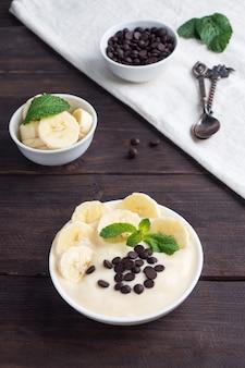 Gezond ontbijt, dessert met melkyoghurtbanaan en chocolade op een bord. donkere houten achtergrond.