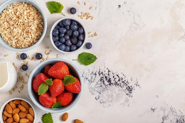 Gezond ontbijt - een kom van havermout, bessen en fruit, bovenaanzicht.