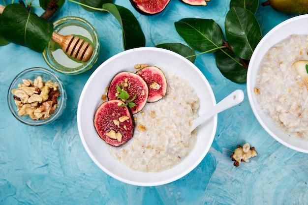 Gezond ontbijt. een kommen pap met plakjes peer en walnoten en pap met vijgen op blauwe achtergrond. twee kommen. plat liggen. kopieer ruimte. bovenaanzicht.