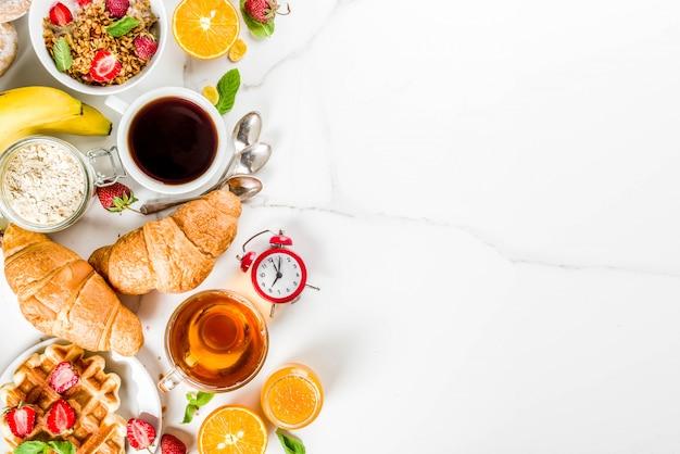Gezond ontbijt eten concept, verschillende ochtend eten - pannenkoeken, wafels, croissant havermout sandwich en muesli met yoghurt, fruit, bessen, koffie, thee, jus d'orange, witte achtergrond