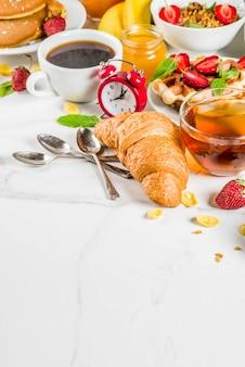 Gezond ontbijt eten concept, verschillende ochtend eten - pannenkoeken, wafels, croissant havermout sandwich en muesli met yoghurt, fruit, bessen, koffie, thee, jus d'orange