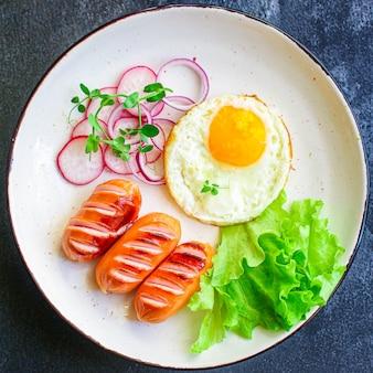 Gezond ontbijt, gebakken eieren, worstjes en groenten