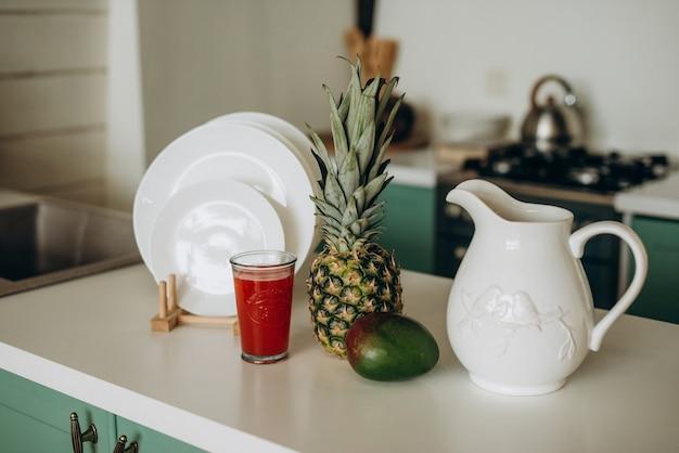 Gezond ontbijt, glas verse grapefruit, mango, ananas wit vaatwerk. zachte selectieve aandacht.