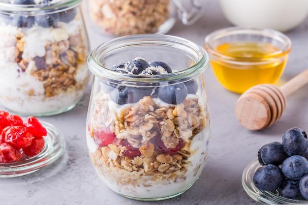 Gezond ontbijt - glazen potten havervlokken met vers fruit, yoghurt en honing