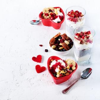 Gezond ontbijt - granaatappel, yoghurt, granolaparfait op concrete achtergrond. romantische tijd.