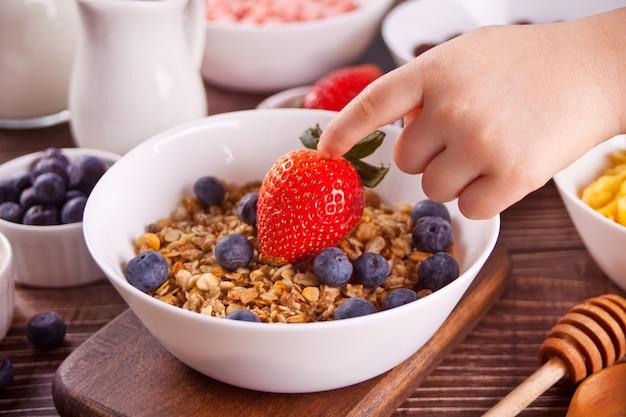 Gezond ontbijt. granola, muesli met verse bessen. de hand van het kind raakt een aardbei aan.