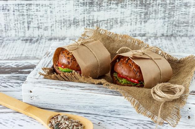 Gezond ontbijt - hamburger met gerookte zalm, slablaadjes en avocado geserveerd in een ambachtelijk papier op houten ondergrond, horizontaal.
