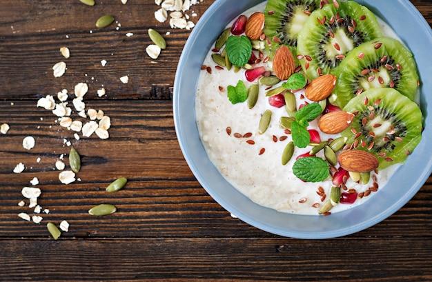 Gezond ontbijt. havermout met kiwi, granaatappel, lijnzaad en noten. detox-menu. bovenaanzicht plat leggen