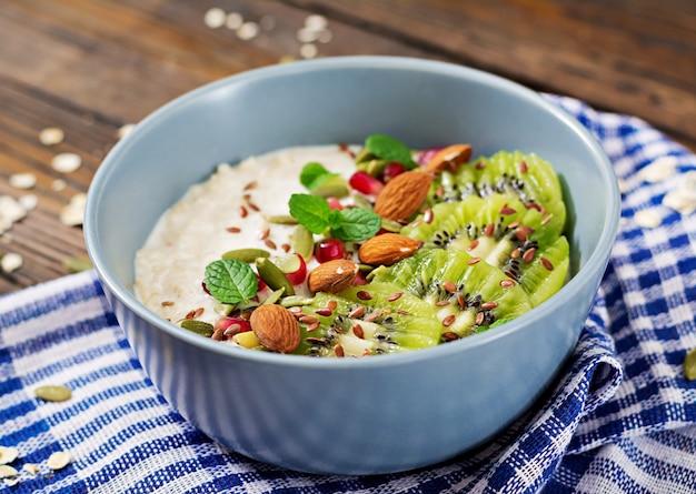 Gezond ontbijt. havermout met kiwi, granaatappel, lijnzaad en noten. detox-menu.