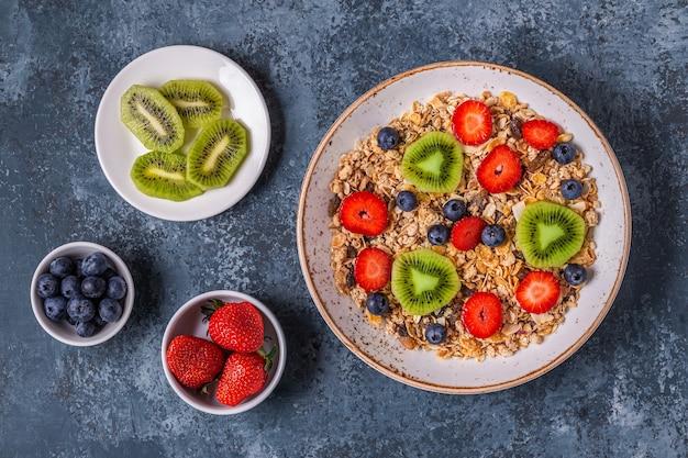 Gezond ontbijt, kom met havergranola en bessen, bovenaanzicht.