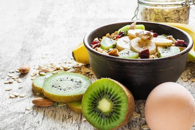Gezond ontbijt. kom zelfgemaakte havermout met fruit, bessen, noten en ei