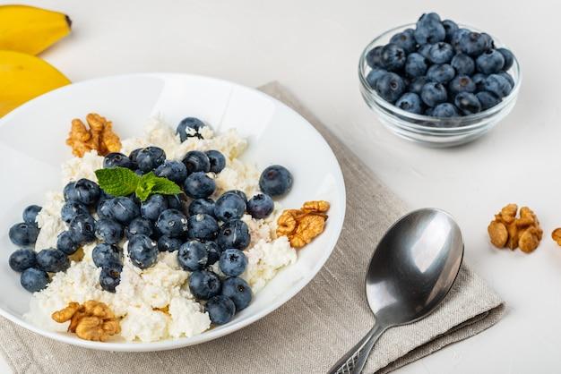 Gezond ontbijt. kwark met bosbessen, noten, honing en munt in een witte kom