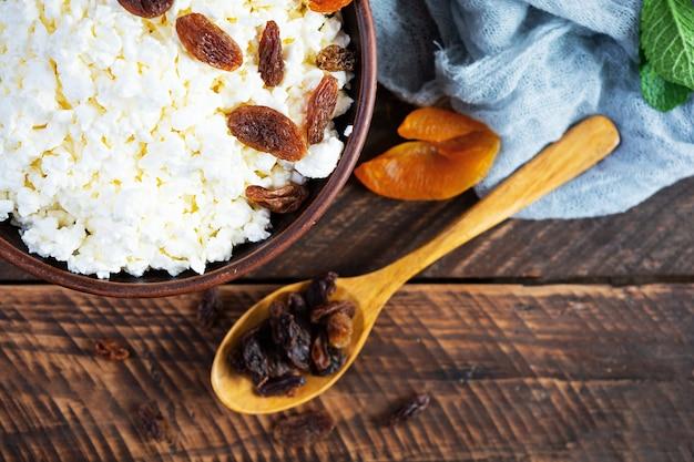 Gezond ontbijt kwark met rozijnen, gedroogde abrikozen, amandel, cashew en munt