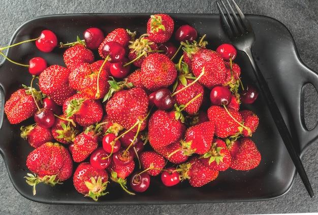 Gezond ontbijt, lunch of snack. zomerbessen en fruit. biologische verse kersen en aardbeien op een rechthoekige schotel, met een vork, op een zwarte stenen tafel. bovenaanzicht