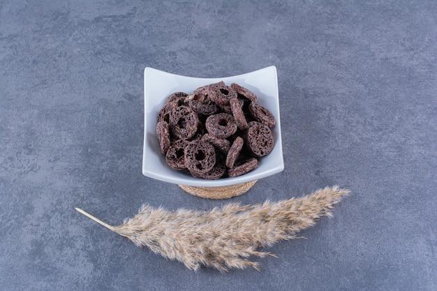 Gezond ontbijt met chocolade maïs ringen in een plaat op een steen.