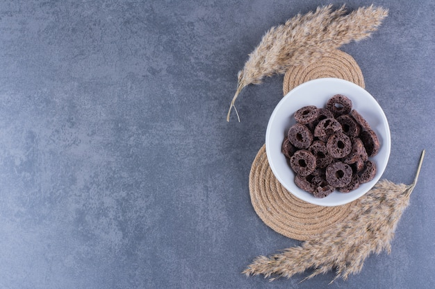 Gezond ontbijt met chocolade maïs ringen in een plaat op een stenen oppervlak