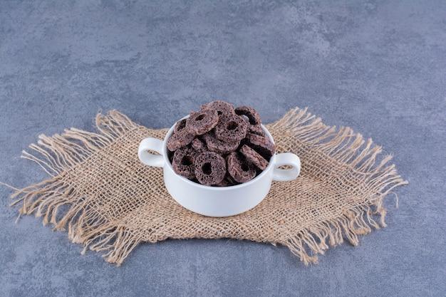 Gezond ontbijt met chocolade maïs ringen in een plaat op steen.