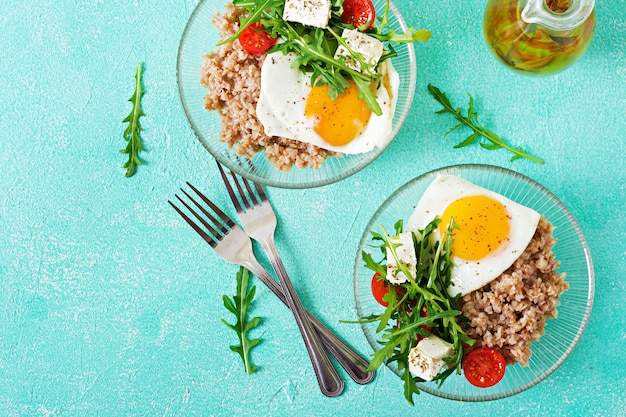 Gezond ontbijt met ei, feta-kaas, rucola, tomaten en boekweitpap op lichte achtergrond. goede voeding. dieet menu. plat leggen. bovenaanzicht