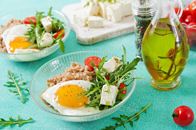 Gezond ontbijt met ei, feta-kaas, rucola, tomaten en boekweitpap op lichte achtergrond. goede voeding. dieet menu.