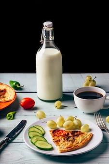Gezond ontbijt met frittata, fruit, groenten, melk en kopje koffie op lichte houten.