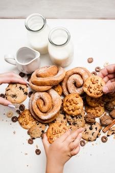 Gezond ontbijt met gebak, close-up bovenaanzicht. familie die volkoren scones neemt van puinhoop van bakkerijvoedsel op tafel in de buurt van flessen en kruik melk