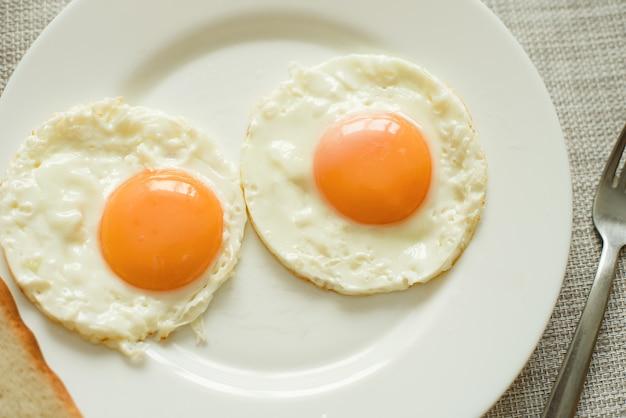 Gezond ontbijt met gebakken eieren op houten tafel