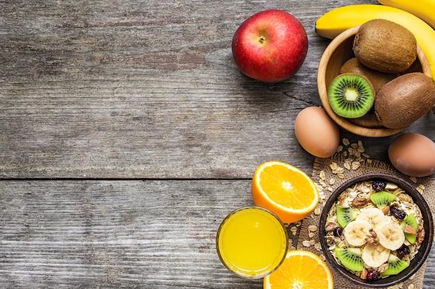 Gezond ontbijt met haver, fruit, bessen, ei en sinaasappelsap