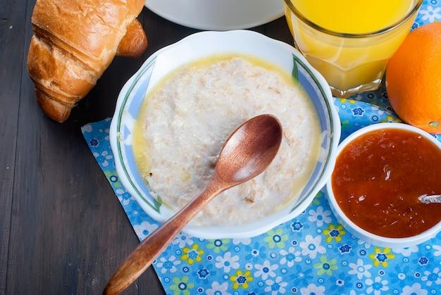 Gezond ontbijt met havermout met boter, croissant en koffie