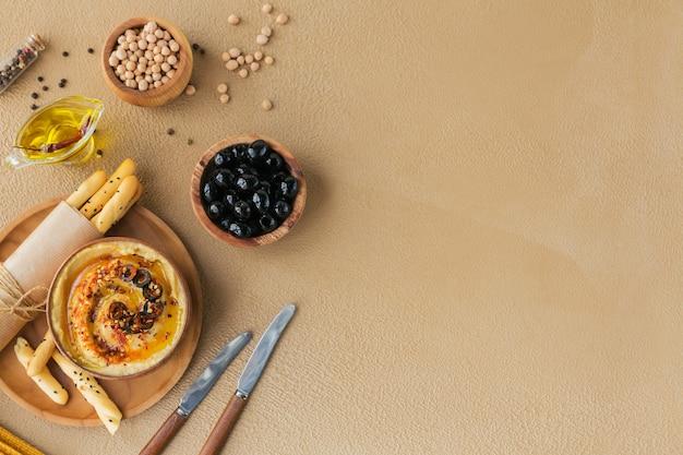 Gezond ontbijt met huisgemaakte hummus, zwarte olijven en knäckebröd. dieet en gezonde snacks.