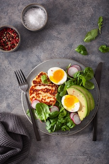 Gezond ontbijt met keto paleo-dieet: gekookt ei, avocado, halloumi-kaas, slablaadjes