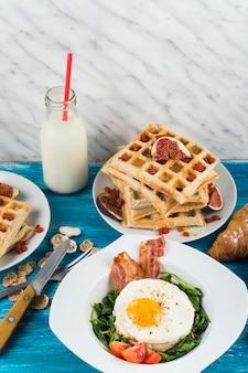 Gezond ontbijt met melkfles op houten lijst tegen marmeren geweven achtergrond