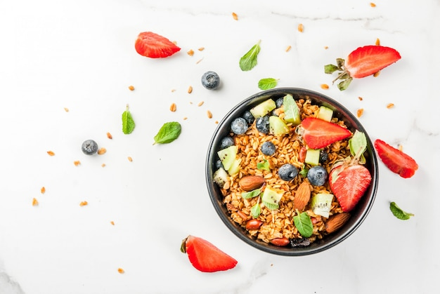 Gezond ontbijt met muesli of granola met noten en verse bessen en fruit aardbei, bosbessen, kiwi, op witte tafel, bovenaanzicht