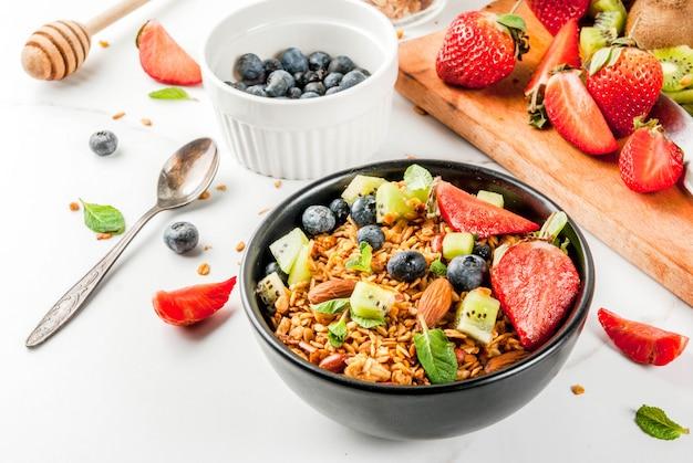 Gezond ontbijt met muesli of granola met noten en verse bessen en fruit aardbei, bosbessen, kiwi, op witte tafel,