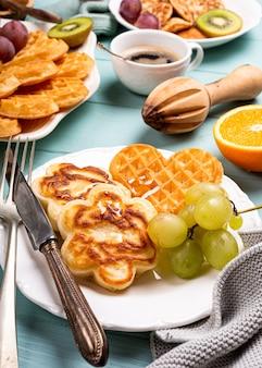 Gezond ontbijt met verse warme wafels harten, pannenkoeken bloemen met bessenjam en fruit op turquoise oppervlak, bovenaanzicht, plat leggen. voedsel concept