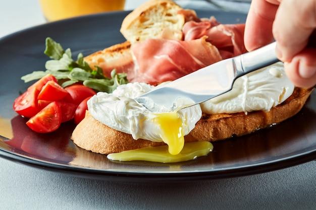 Gezond ontbijt met volkorenbrood, toast en gepocheerd ei. iemands hand met een mes dat een ei snijdt