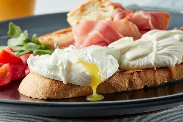 Gezond ontbijt met volkorenbrood toast en gepocheerd ei met groene salade, spek en plakjes tomaat