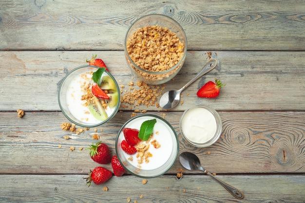 Gezond ontbijt met yoghurt, bessen en granola op de houten mening van de lijstbovenkant