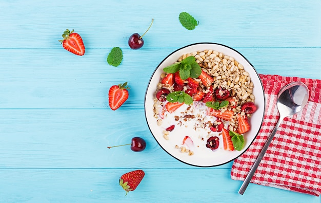Gezond ontbijt - muesli, aardbeien, kersen, noten en yoghurt in een kom op een houten tafel. vegetarisch concept eten. bovenaanzicht