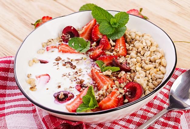 Gezond ontbijt - muesli, aardbeien, kersen, noten en yoghurt in een kom op een houten tafel. vegetarisch concept eten.