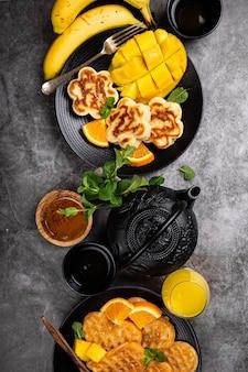 Gezond ontbijt oppervlak met verse warme wafels harten, pannenkoeken bloemen met bessen honing en exotisch fruit over grijs, bovenaanzicht, plat leggen. gezond voedselconcept met exemplaarruimte