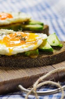 Gezond ontbijt. sandwich met roggebrood, avocado en gebakken eieren