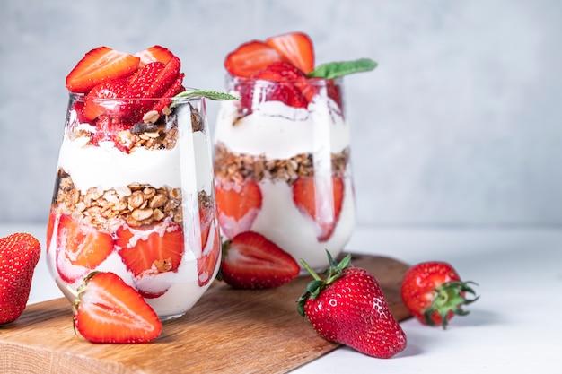 Gezond ontbijt van aardbeienparfaits gemaakt met verse aardbeienyoghurt en muesli in glazen
