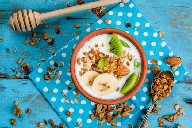 Gezond ontbijt: yoghurt met granola, banaan en kiwi