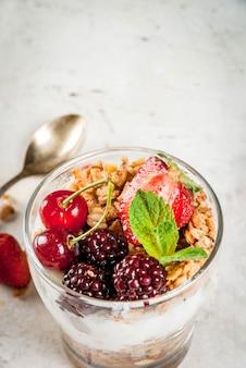 Gezond ontbijt. zomer bessen en fruit. zelfgemaakte griekse yoghurt met granola, bramen, aardbeien, kersen en munt. op witte betonnen stenen tafel, in glazen. kopieer ruimte dichtbij bekijken