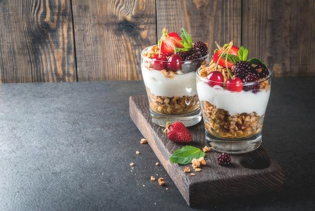 Gezond ontbijt. zomerbessen en fruit. zelfgemaakte griekse yoghurt met granola, bramen, aardbeien, kersen en munt. op houten en stenen zwarte tafel, in glazen.