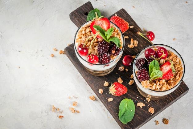 Gezond ontbijt. zomerbessen en fruit. zelfgemaakte griekse yoghurt met granola, bramen, aardbeien, kersen en munt. op witte betonnen stenen tafel, in glazen. bovenaanzicht