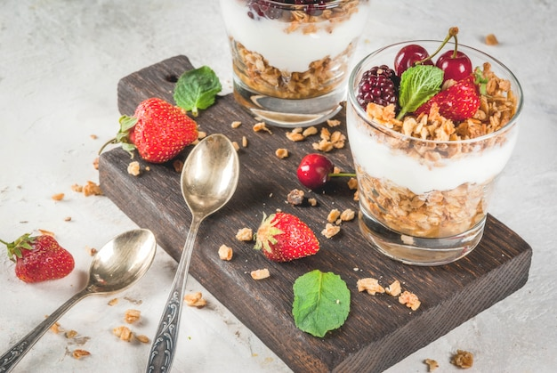 Gezond ontbijt. zomerbessen en fruit. zelfgemaakte griekse yoghurt met granola, bramen, aardbeien, kersen en munt. op witte betonnen stenen tafel, in glazen.