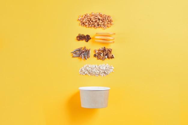 Gezond ontbijtconcept, document kom met granola, noten, tarwe op kleurenachtergrond.