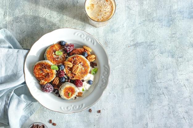 Gezond ontbijtconcept. kaaspannenkoekjes met bosbessen, bramen, chocolade en muntblaadjes