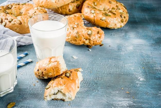 Gezond ontbijtconcept, naar huis gemaakte graangewassenongezuurde broodjes met melkglas, op blauwe achtergrond